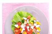 Appetizing fish salad with vegetables on plate isolated on white
