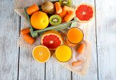 Fruit and vegetable juice and fresh vegetables and fruits on napkin and in wooden box on wooden background
