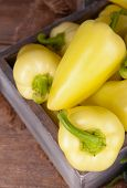Yellow peppers in crate with sackcloth on table close up