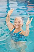 Senior woman lifting her arms in aqua fitness class in a swimming pool