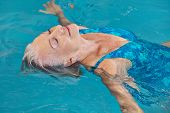 Happy senior woman relaxing in swimming pool with water yoga