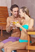 Happy couple in holidays drinking cocktails on swimming pool