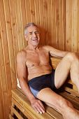 Smiling old man sitting sweating in a sauna in his holidays