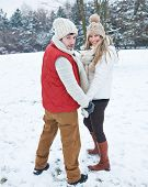 Happy couple hiking together through snow in winter