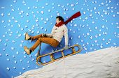 picture of toboggan  - Happy young man on sled having fun against the blue background with snowflakes - JPG