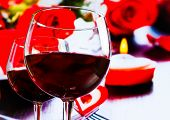 Two Red Wine Glasses On Blur Hearts And Roses Decoration Background