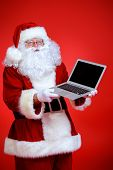 Modern Santa Claus using laptop computer over red background. Christmas.