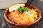 Bowl of boiled rice and fresh salted salmon on bamboo mat background