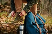 picture of thermos  - Female hiker tying shoelaces outdoors in autumn forest near thermos and backpack - JPG