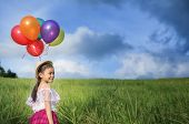Young Asia Girl Holds Tightly To A Large Bunch Of Helium Filled Balloons