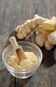 ginger root and ground ginger spice on wooden background