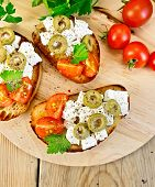 Sandwich with feta and olives on table