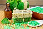 Soap homemade and oil with nettles in mortar on board