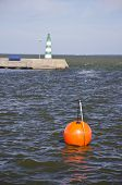 Orange Buoy And Lighthouse In Sea Dock