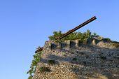 Rusty metallic iron beam on a stone wall.