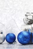 Decorative Christmas ball and gift on abstract glitter silver background