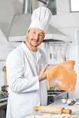 Portrait of confident male chef holding ravioli pasta sheet at counter in commercial kitchen