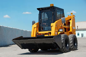 stock photo of skid-steer  - skid steer loader construction machine with bucket outdoors - JPG