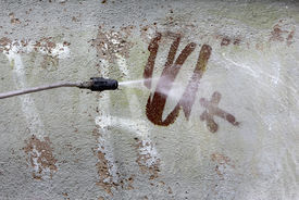 picture of swastika  - Cleaning graffiti with a brush and water - JPG