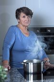 foto of grandma  - Picture of worried grandma standing in the kitchen