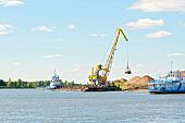picture of barge  - Loading sand with the help of a crane on a barge on the water and sky background of yellow sand - JPG