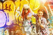 pic of teenagers  - Two happy teenage girls eating ice cream by colorful painted wall on sunny summer day - JPG