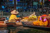 picture of floating  - Unidentifiable Thai woman sells fruit from a boat at the Floating Market in Damnoen Saduak - JPG