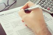 stock photo of income tax  - Man filling individual income tax return form - JPG