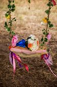 image of swing  - wedding bouquet on a wooden swing swing hanging on a tree branch entwined with flowers - JPG
