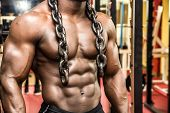 foto of arm muscle  - Attractive hunky black male bodybuilder doing bodybuilding pose in gym with iron chains over shoulders - JPG
