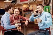 image of over counter  - Important call during meeting with friends. Three young men sitting at the bar counter and drinking beer while one of them talks over the phone