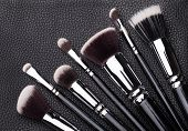 stock photo of leather tool  - Set of professional makeup brushes over black leather background - JPG
