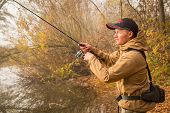 stock photo of freshwater fish  - Fisherman on the river bank - JPG