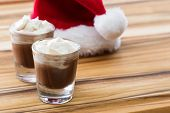 stock photo of peppermint  - holiday shooters chocolate and peppermint on a wooden background with a red santa hat - JPG