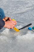 stock photo of ice fishing  - Ice fishing. Winter fishing, fisherman holding a fishing rod winter.  Wants to catch the fish. ** Note: Shallow depth of field - JPG