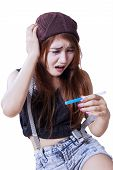 image of promiscuous  - Portrait of worried teenage girl sitting on the floor while holding a pregnancy test - JPG
