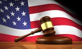 stock photo of law order  - American law and justice concept with a 3d rendering of a gavel on a wooden desktop and the United States Of America flag on background - JPG