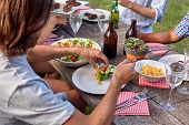 stock photo of gathering  - man dishing healthy fresh salad at outdoor barbecue garden party gathering - JPG