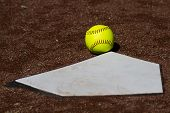 image of fastpitch  - A fair ball as a yellow fastpitch ball is in fair territory in front of homeplate - JPG