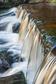 stock photo of h20  - A small moorland stream cascading over a weir captured using a slow shutter speed to blur the movement of the water - JPG