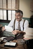 image of 1950s style  - Smiling reporter working at office desk with vintage typewriter 1950s style - JPG