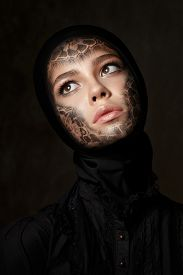 stock photo of wraith  - Portrait of young beautiful woman with faceart over dark background - JPG