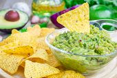 picture of nachos  - Bowl with chunky guacamole served with nachos and ingredients on backgroung - JPG