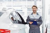 Portrait of smiling male automobile mechanic holding clipboard while standing by car in repair shop poster