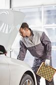 Young automobile mechanic examining car in automobile shop poster