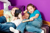 Three children �¢�?�? sisters - playing video games in their room