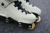 picture of inline skating  - pair of white aggressive skates on asphault - JPG