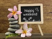 stack of pebbles and mini blackboard with text happy weekend poster