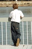 Young Boy Looking Upon the Ocean Reflecting on Life