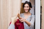 Cheerful young woman in casuals trying new clothes in changing room of a boutique. Smiling girl buyi poster